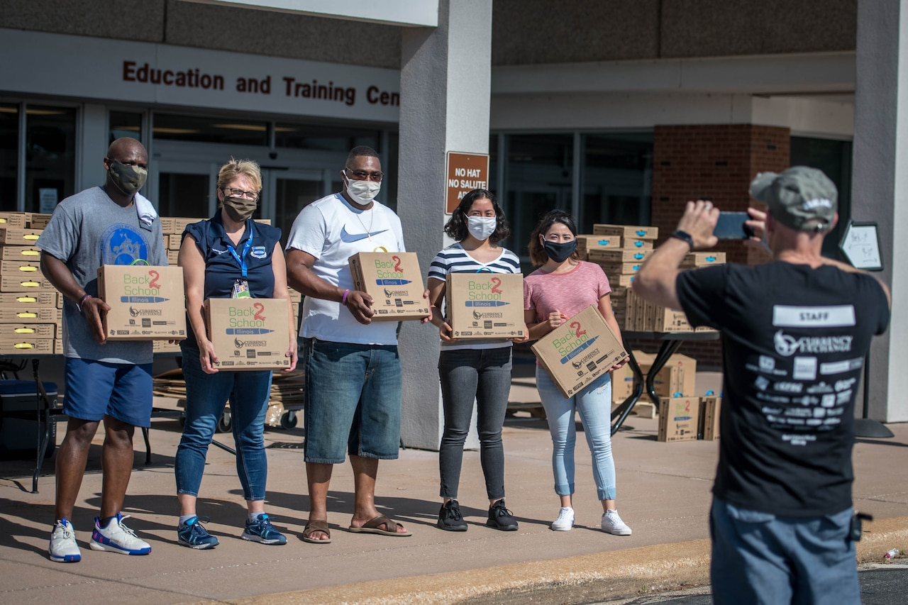 Five people, holding boxes, stand in front of the education center for a group photo.