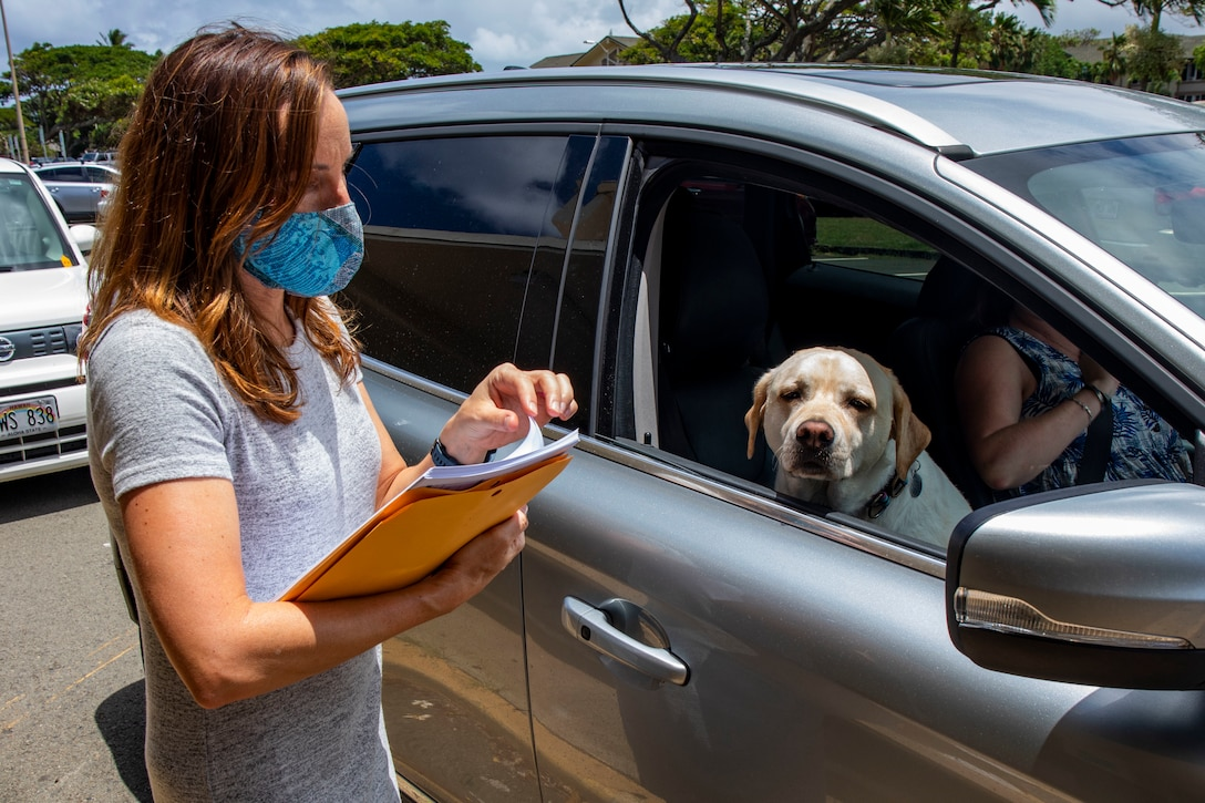 A masked woman, holding papers, talks to a driver in a car.