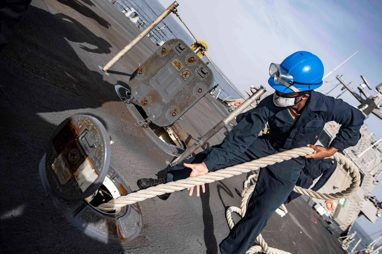A sailor in a blue hard hat pulls a rope from inside a ship.