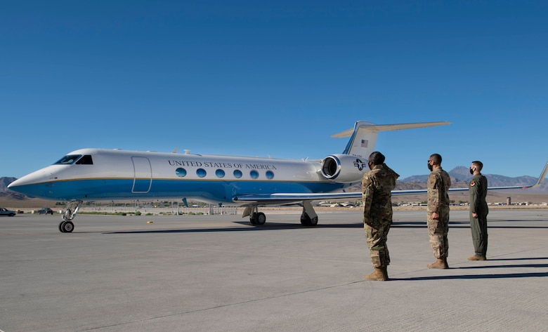 Leadership from Creech Air Force Base salute the aircraft carrying Secretary of the AF Barrett on the flight line.