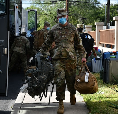 Soldier carrying bags from bus.