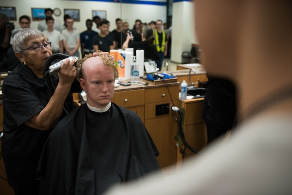 Airmen getting head shaved by civilian barber