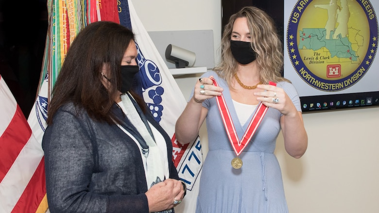 Patti Williams' daughter Cassi presents her with a De Fluery medal, the U.S. Army Engineer Association's most prestigious award.