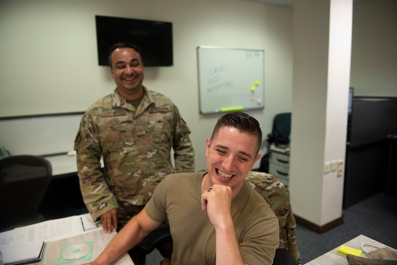 Photo of two Airmen working at a desk.