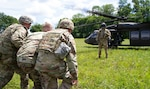 Kentucky National Guard Soldiers with the 617th Military Police Company help a simulated injured person to a UH-60 Black Hawk helicopter during casualty evacuation training at Blue Grass Army Depot in Richmond, Ky., Aug. 12, 2020.