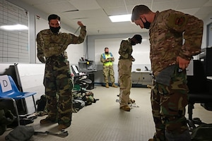 Airmen put on mopp gear during an exercise.