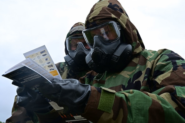 Airmen in mopp gear read an Airman's Quick Reference Guide.