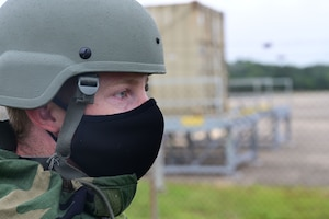 An Airman in a helmet looks off in the distance