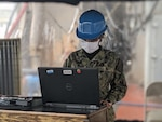 A sailor aboard the USS Tortuga (LSD-46) uses a damage control stand-alone laptop provided by Naval Surface Warfare Center, Philadelphia Division (NSWCPD) in the fight against COVID-19.  The laptop utilizes NSWCPD's Advanced Damage Control System (ADCS), which provides crews aboard U.S. Navy vessels the capability to track personnel, plot boundaries around quarantined areas, and manage traffic throughout the ship. (U.S. Navy Courtesy Photo)