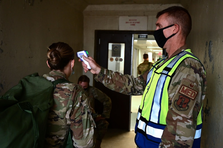 An Airman checks the temperature of other Airmen before entering a building.
