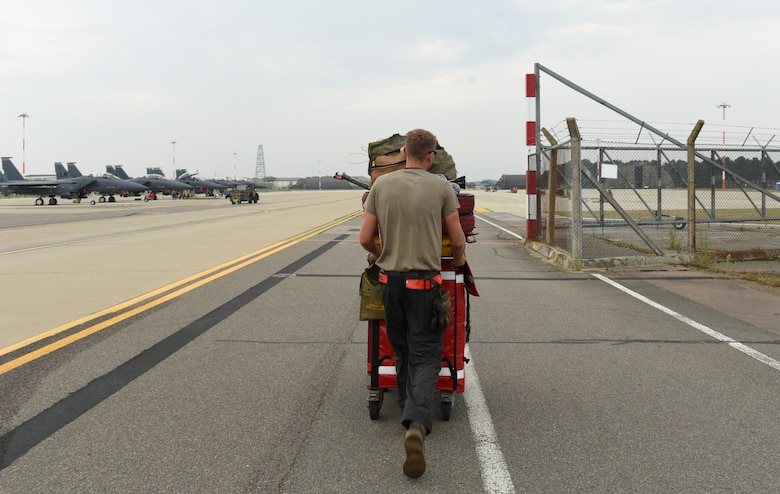 An Airman assigned to the 48th Aircraft Maintenance Squadron transports tools to the newly expanded F-15E parking ramp at Royal Air Force Lakenheath, England, Aug. 11, 2020. The ramp expansion facilitates construction of new infrastructure for the F-35A Lightning II arriving in late 2021. (U.S. Air Force photo by Airman 1st Class Rhonda Smith)