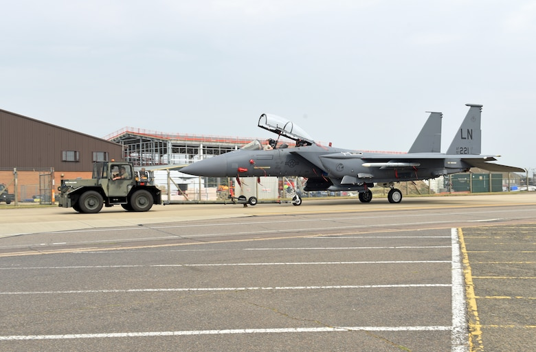 An F-15E Strike Eagle assigned to the 48th Fighter Wing is moved to the newly expanded parking ramp at Royal Air Force Lakenheath, England, Aug. 11, 2020. The ramp's completion signified another key milestone as the 48th Fighter Wing prepares to welcome its first F-35A aircraft in late 2021. (U.S. Air Force photo by Airman 1st Class Rhonda Smith)