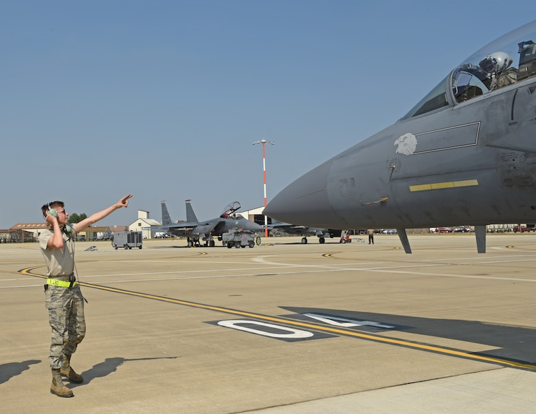 A 48th Fighter Wing crew chief marshalls an F-15E Strike Eagle onto a newly expanded parking ramp at Royal Air Force Lakenheath, England, Aug. 12, 2020. The ramp consolidates F-15E Strike Eagle operations for the two squadrons, shortens transit times and maintenance operations, and improves mission efficiency. (U.S. Air Force photo by Airman 1st Class Rhonda Smith)
