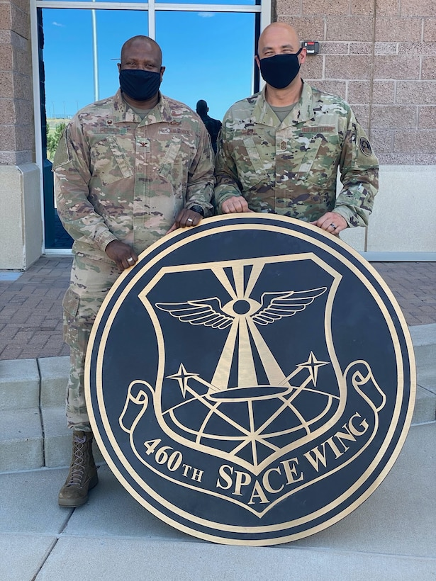 """Col. Devin Pepper, Buckley Garrison commander, and Chief Master Sgt. Robert Devall, Buckley Garrison command chief, pose for a photo with the 460th Space Wing sign at the Headquarters building on Buckley Air Force Base, Colo., August 7, 2020.  The sign was taken down, along with the other 460th Space Wing signs and shields to mark """"the end of an era."""" The 460th was deactivated and Buckley Garrison was activated during a virtual ceremony on July 24. (U.S. Air Force photo by Staff Sgt. Jessica Kind)"""