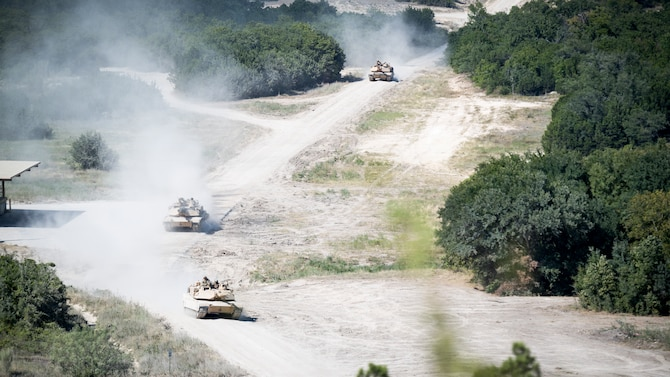 Three U.S. Army M1 Abrams tanks drive down a road during Exercise Pegasus Forge at Fort Hood, Texas, Aug. 11, 2020. The event took 45 days in the field leading up to the last full day filled with a fires coordination exercise. (U.S. Air Force photo by Senior Airman Lillian Miller)