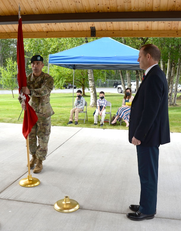 Col. Damon Delarosa, commander of the U.S. Army Corps of Engineers – Alaska District, prepares to place the guidon in the stand in front of Randy Bowker, chief of the Program and Project Management Division, signifying the start of his command of the Alaska District today during a ceremony at the headquarters building on Joint Base Elmendorf-Richardson.