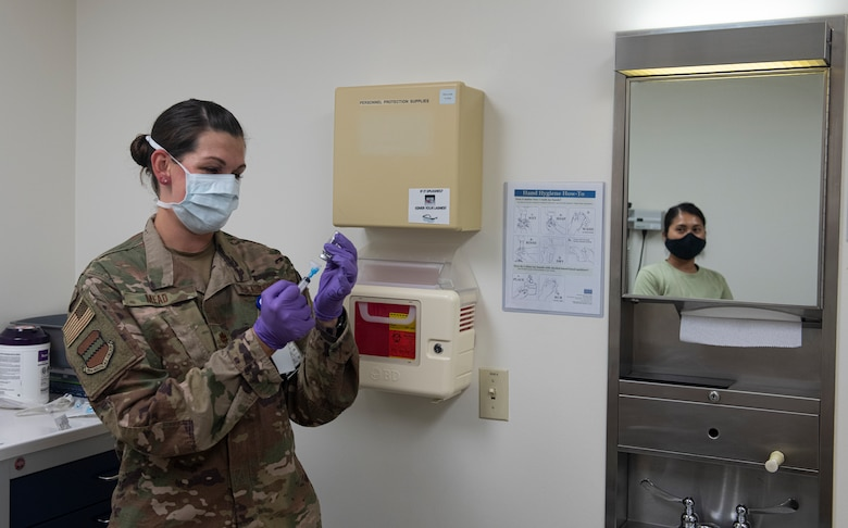 Airman prepares to give another Airman a shot.