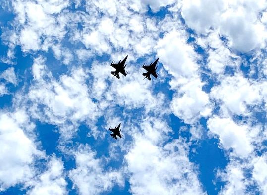 """F-16 pilots assigned to the 457th Fighter Squadron, 301st Fighter Wing, performed a memorial flyover at Dallas Fort Worth National Cemetery to honor POW and F-16 program founder, Brigadier General Lyle Cameron on August 7. They flew a """"missing man"""" formation flyover for his remaining family members, friends and those in attendance. (U.S. Air Force photo by Capt. Jessica Gross)"""