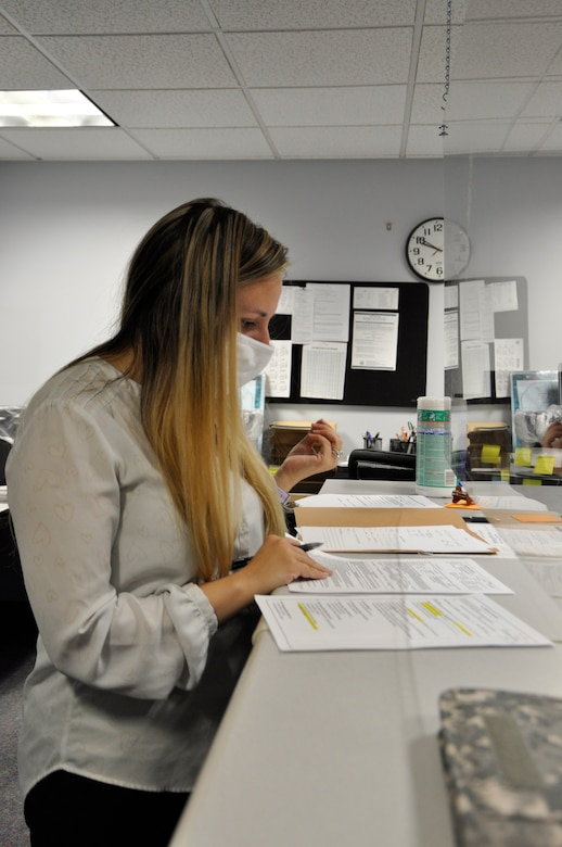 Woman reviews pay documents behind a glass shield.
