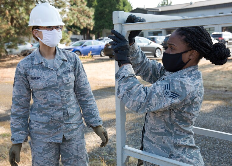 Airmen assembly a plastic tray cart as part of setting up a field kitchen.