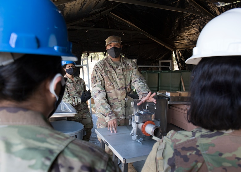 Airmen talk inside field kitchen after setting it up.