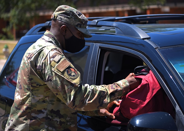 U.S. Air Force Col. James Finlayson, 17th Training Wing vice commander, gives a backpack to a military member during Operation Back to School on Goodfellow Air Force Base, Texas, Aug. 12, 2020. Finlayson and other members of Goodfellow assisted in handing out backpacks filled with supplies to families to assist with preparing children for school. (U.S. Air Force photo by Airman 1st Class Ethan Sherwood)
