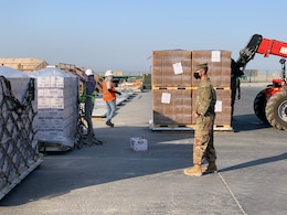 In response to the tragedy in Lebanon, 1st. Lt. Morgan Kim, distribution integration branch operations officer, 1st Theater Sustainment Command, ensures supplies are ready for transport at Camp Arifjan, Kuwait, Aug. 5, 2020. In less than 24 hours, the 1st TSC packaged and shipped more than 21,000 cases of culturally appropriate meals, 5,700 cases of bottled water, 670 cases of health and comfort packs, and three pallets of medical supplies.