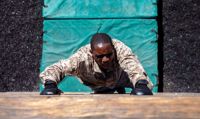 A recruit with Lima Company, 3rd Recruit Training Battalion, climbs over an obstacle during the Confidence Course at Marine Corps Recruit Depot, San Diego, Aug. 10, 2020.