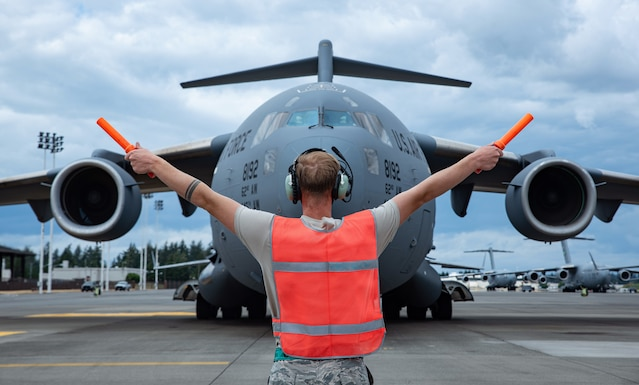 Airman 1st Class David Newgent, 62nd Aircraft Maintenance Squadron crew chief, marshals a C-17 Globemaster III to its parking spot during Exercise Long Hammer/Rainier War at Joint Base Lewis-McChord, Wash., Aug. 10, 2020. Exercises like this maintain Team McChord's readiness to deploy and operate anywhere anytime. (U.S. Air Force photo by Senior Airman Tryphena Mayhugh)