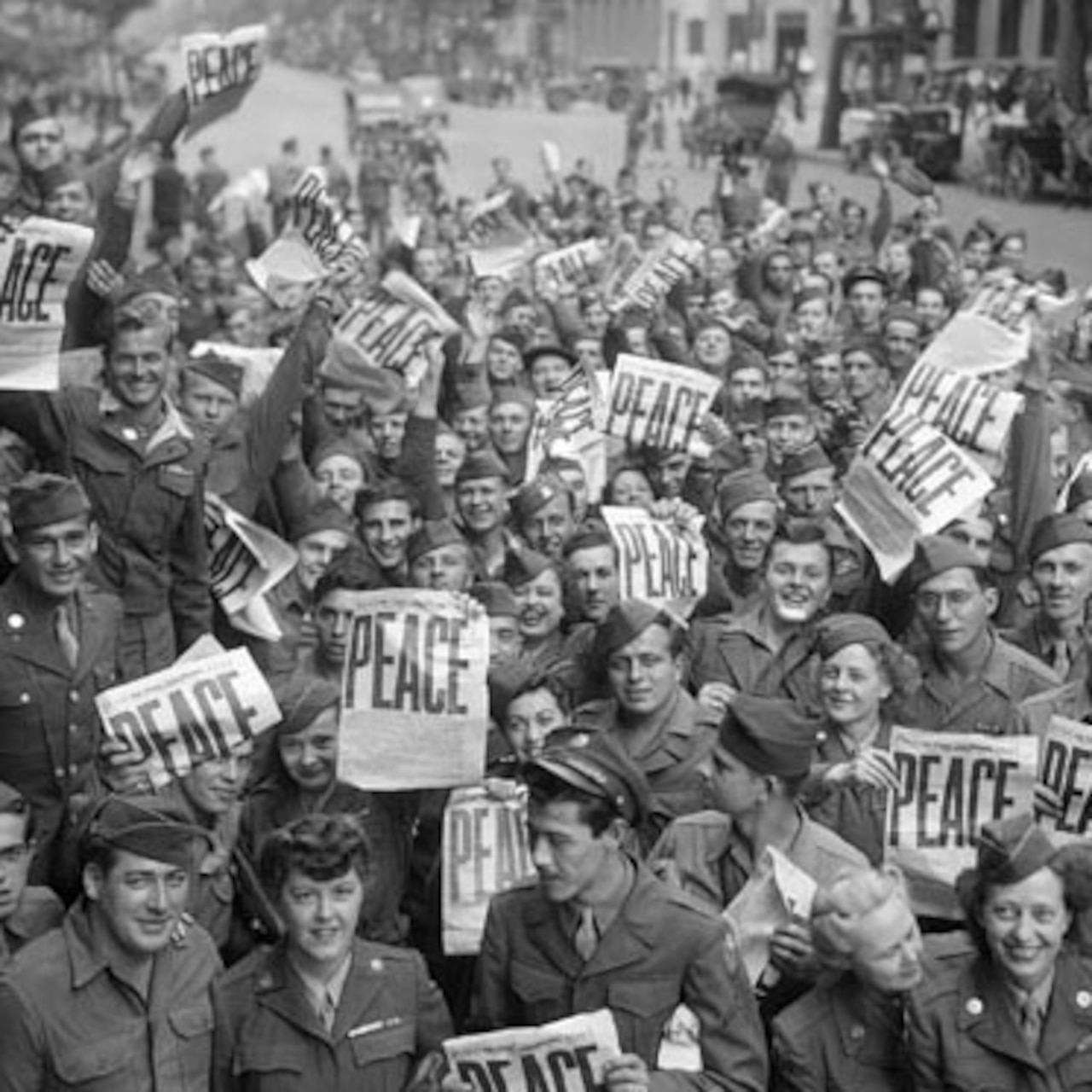 "A crowd of people on a city street smile and hold up newspapers with headlines that say ""PEACE"" in big letters."