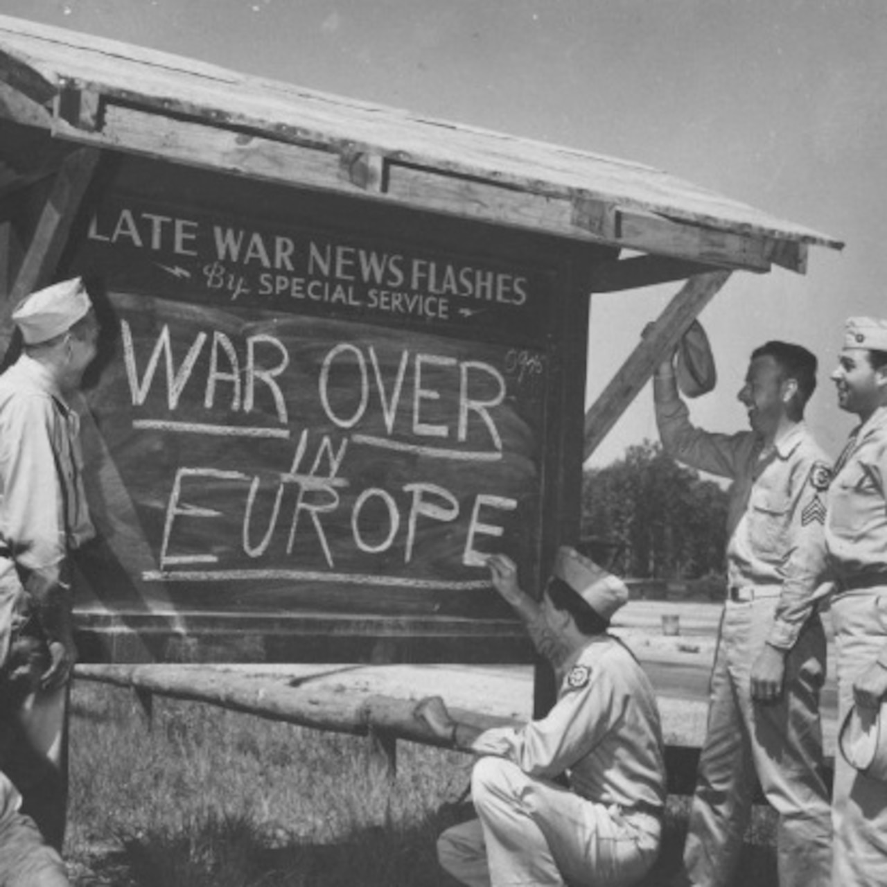 "Smiling troops gather round a chalkboard posted outside with ""WAR OVER IN EUROPE"" written on it."