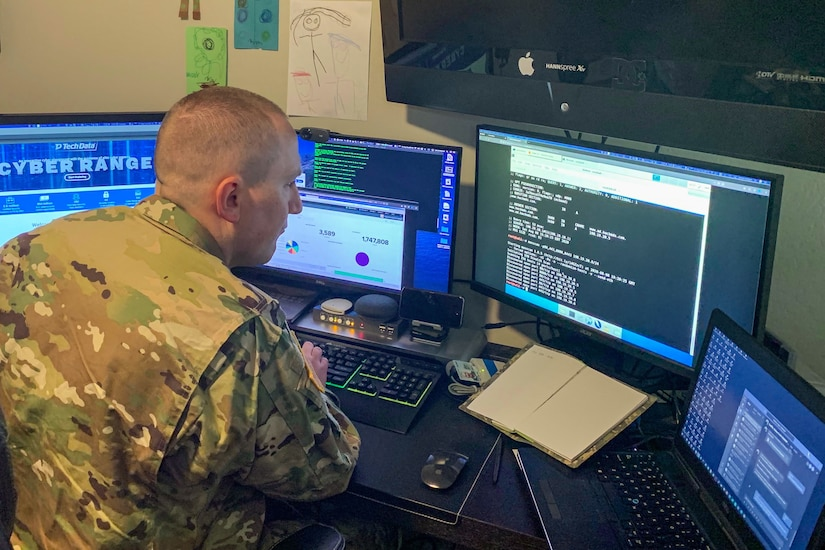 A soldier works at a computer station with four monitors.
