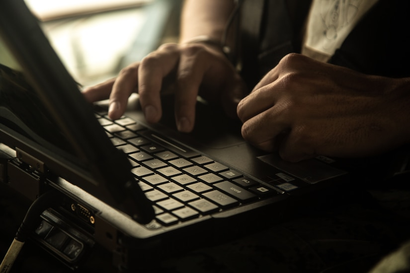 A Marine's hands on a laptop computer's keyboard.