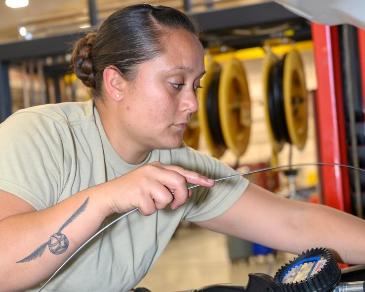 An Airman checks engine fluid levels inside an engine bay of a vehicle.