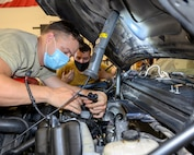 Two Airmen inspect wiring in an engine as part of routine and preventative maintenance.