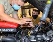 Two Airmen conduct routine vehicle maintenance in a engine bay of a vehicle.