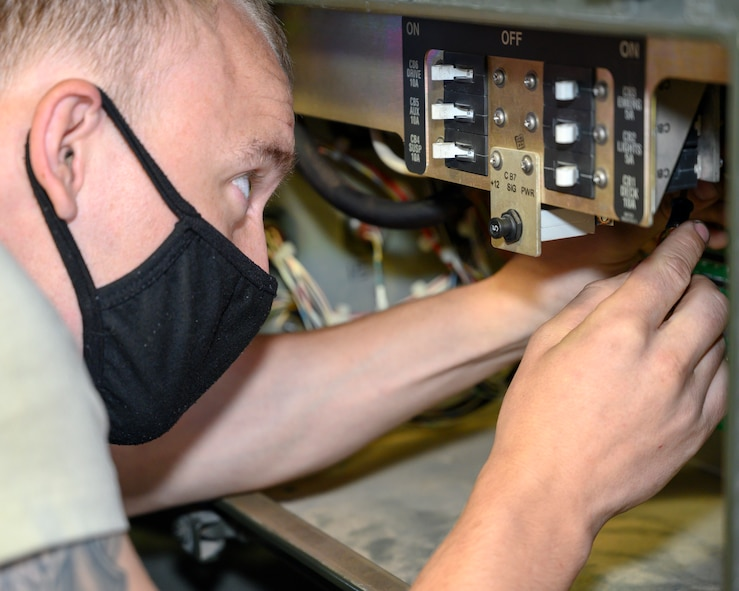 An Airman inspects the electrical system of a Tunner loader.