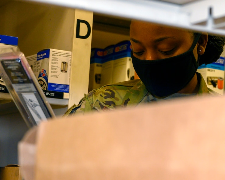 An Airman looks over vehicle parts while doing inventory.