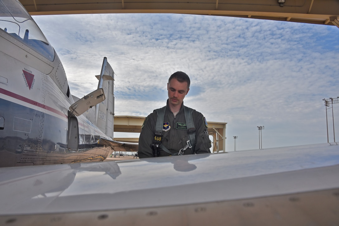 "First Lt. Ralph ""Bo"" Korpman looks over an Air Force plane before takeoff."