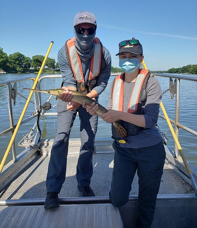 Summer hires Dayla Dillon and Joshua Jacobs pose with a longnose gar while electrofishing along the Kankakee River.