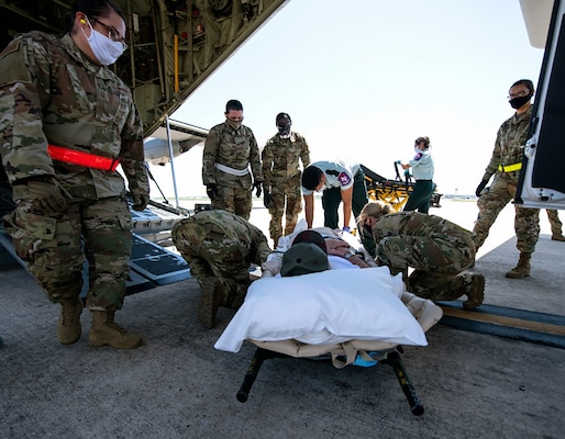One of eight spinal cord injury patients from Audie Murphy Veterans Affairs Medical Center, South Texas Veterans Health Care System, San Antonio, Texas, is moved onto a U.S. Air Force C-130 aircraft at Joint Base San Antonio-Lackland July 14, for a brief flight to Dallas Love Field Airport, Texas.