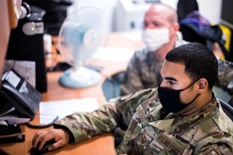 Photo of Airman assisting another Airman on a computer