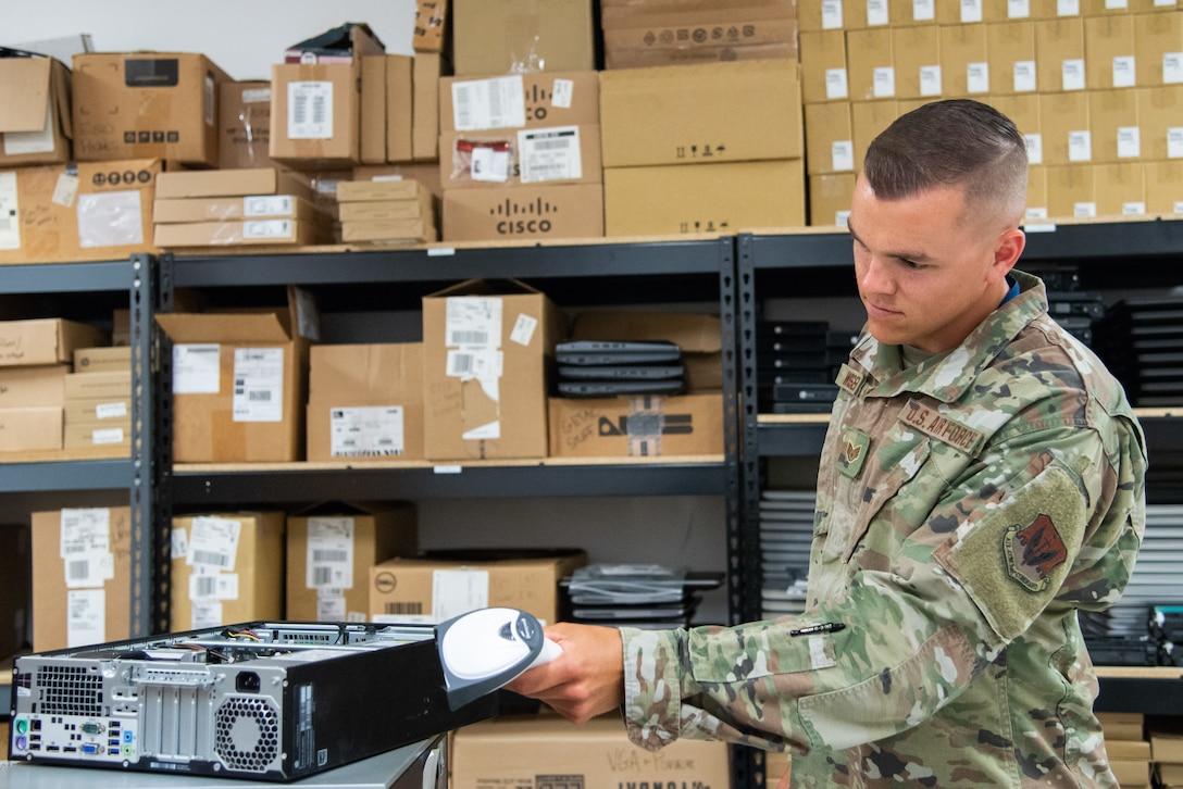 A photo of Staff Sgt. Jordan J. Wisser scanning the case of a computer.