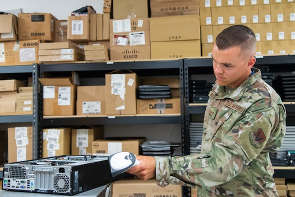 A photo of Staff Sgt. Jordan J. Wisser scanning the case of a computer.