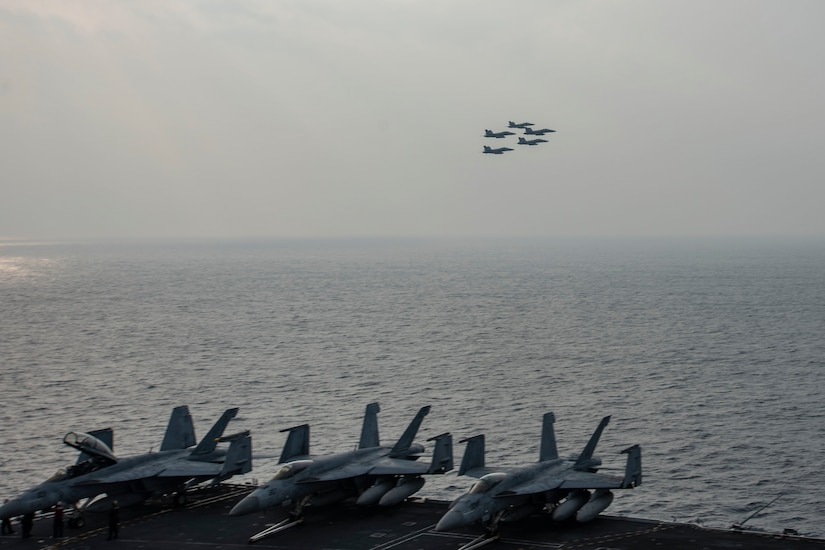 Five aircraft fly above an aircraft carrier at sea.