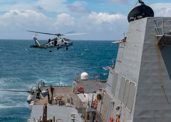 An MH-60R Sea Hawk helicopter assigned to Helicopter Maritime Strike Squadron (HSM) 51 takes off from the flight deck as the Arleigh Burke-class guided-missile destroyer USS Mustin (DDG 89) conducts routine operations.