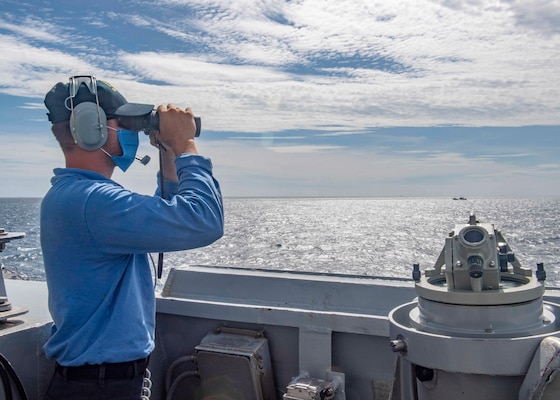 Seaman Zachery Douglas, from Dansville, N.Y., looks through binoculars on the bridge as the Arleigh Burke-class guided-missile destroyer USS Mustin (DDG 89) conducts routine operations.