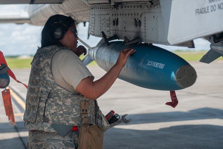 Photo of an Airman loading a munition