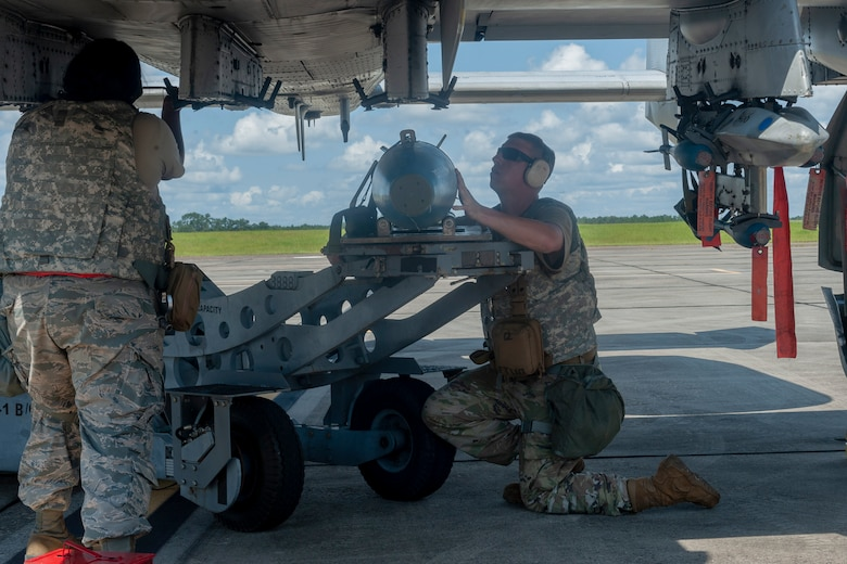 Photo of Airmen loading a munition