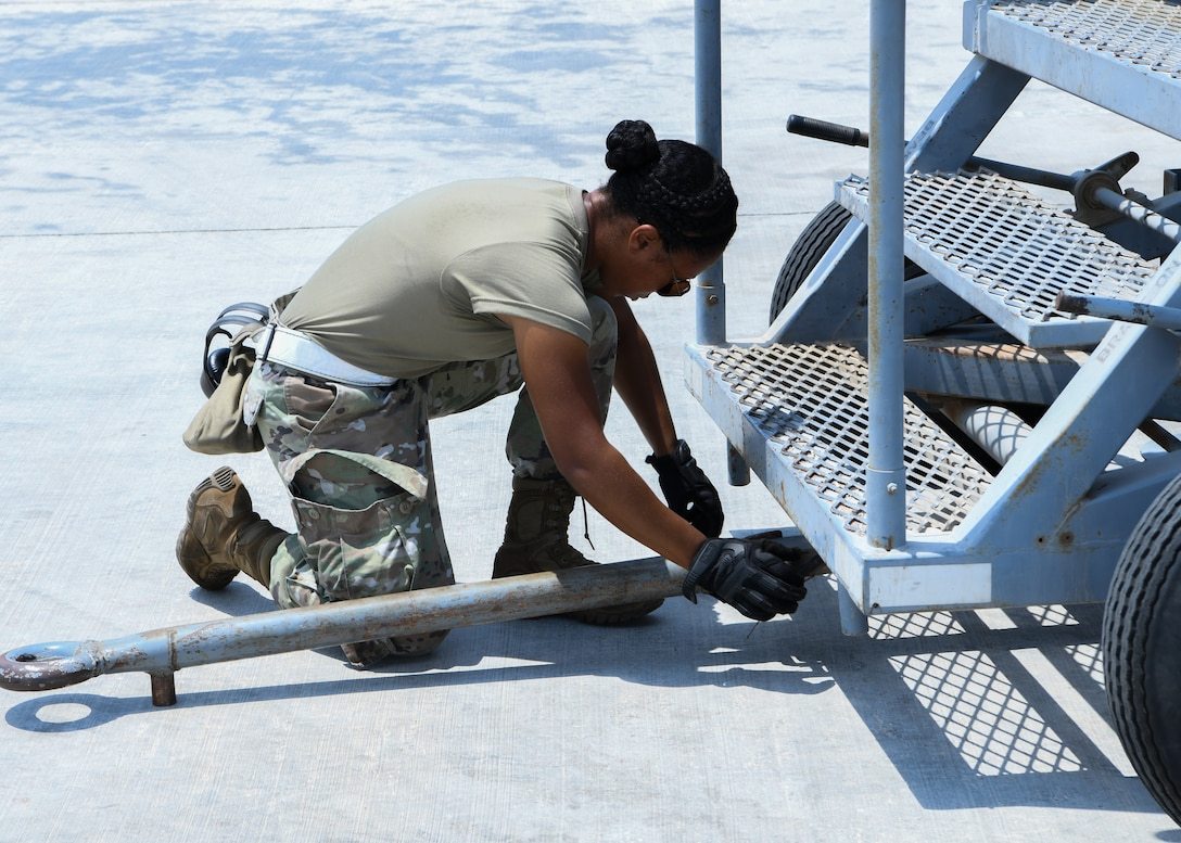 Senior Airman Brittany Cooke-McMath, a 380th Expeditionary Maintenance Squadron KC-10 Extender crew chief, prepares to move stairs before the aircraft takes off at Al Dhafra Air Base, United Arab Emirates, Aug. 18, 2020.